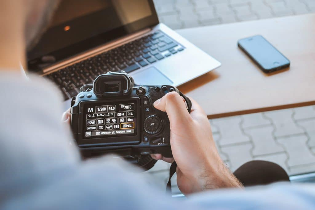 man using a camera - What is Shutter Priority Mode