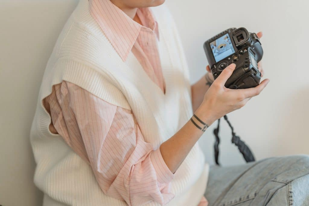 Girl using a camera - How to Use Aperture Priority Mode